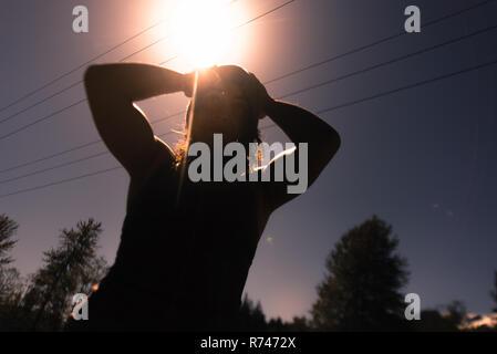 Mujer joven con las manos en la cabeza contra el cielo iluminado por el sol, vista de ángulo bajo retroiluminado Imagen De Stock