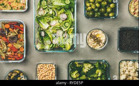 Vegan saludables platos en contenedores. Plano de laicos fresco y cocinado ensalada de verduras, legumbres, frijoles, aceitunas, coles, hummus dip, cuscús para llevar Imagen De Stock