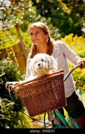 Jovencita en bicicleta con el perro en la cesta Imagen De Stock