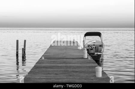 Barco atracado en el muelle al amanecer en impresionante blanco y negro Imagen De Stock