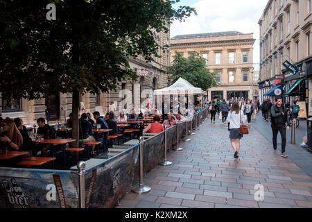Gente sentada fuera comiendo y bebiendo en el Royal Exchange Square, Glasgow Imagen De Stock
