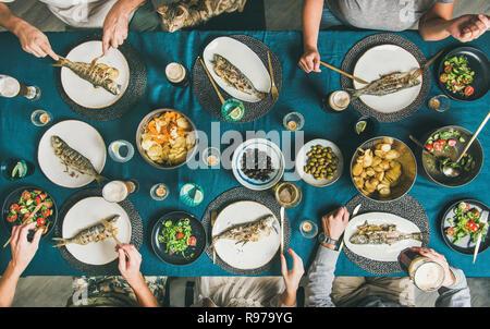 Fish and Chips cerveza parte reunir amigos, comer, beber y celebrar juntos. Flat-lay de manos humanas, cat, vasos de cerveza, lubina a la parrilla f Imagen De Stock
