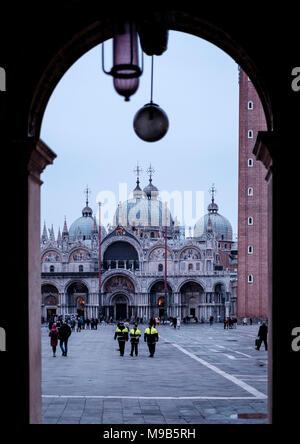 Tres oficiales de policía italianos a pie de la plaza de San Marcos de Venecia, en una noche en marzo Imagen De Stock