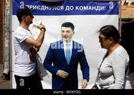 La gente camina más allá de un cartel de la campaña electoral el Primer Ministro ucraniano Volodymyr Groysman en Kiev.Las primeras elecciones parlamentarias tendrán lugar en Ucrania el 21 de julio de 2019. Según las encuestas de opinión, en el 2019 las elecciones parlamentarias de Ucrania 5 Partes será capaz de entrar en el Parlamento ucraniano : El presidente ucraniano Volodymyr Zelensky's partido llamado siervo del pueblo con 41,5%, pro-ruso de la oposición - Plataforma de por vida con el 12,5%, la parte de voz de estrella de rock ucraniano Svyatoslav Vakarchuk con 8,8%, solidaridad europea del ex presidente ucraniano, Petro Poroshenko con 8 Imagen De Stock