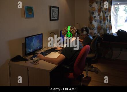 Dos muchachos jugando Dota 2 online video juego en casa con auriculares, Estados Unidos. Imagen De Stock