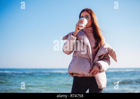 A mediados elegante mujer adulta en la playa bebiendo café para llevar, Odessa, Odeska Oblast, Ucrania Imagen De Stock