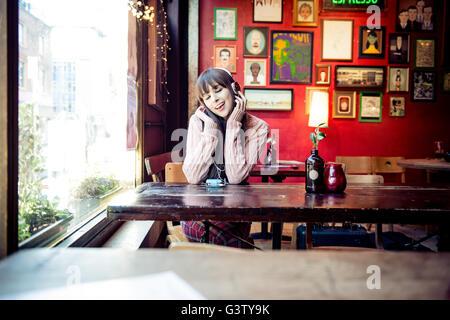 Una joven mujer sentada en una mesa en una cafetería en la ciudad de Manchester. Imagen De Stock