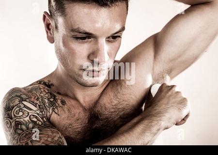 Foto de estudio de mediados de hombre adulto aplicar desodorante Imagen De Stock