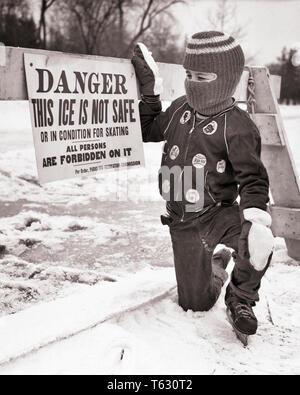 1950 1960 niño usando patines para hielo MÁSCARA DE ESQUÍ MITONES Chaqueta invierno leyendo peligro de hielo no es signo seguro - w4949 HAR001 HARS RIESGO MITONES ATHLETIC B&W TENTACIÓN DESASTRES PROTECCIÓN PELIGROSA ELECCIÓN ADVERTENCIA PASAMONTAÑAS CONCEPTUAL el patinaje sobre hielo, los menores no seguro BLANCO Y NEGRO la etnia CAUCÁSICA HAR001 patines para hielo ANTIGUO Imagen De Stock