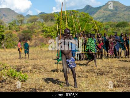 Suri tribu guerrero a bailar durante un donga ritual de combate con palo, valle de Omo Kibish, Etiopía Imagen De Stock