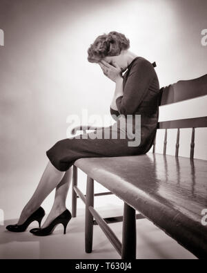 1950 SILUETEADO ANGUSTIADA Mujer sentada en un banco llorando tomados de las manos sobre el rostro tristeza depresión pérdida - s3493 HAR001 HARS potente de ángulo bajo estado de ánimo tristeza AVERGONZADA DUELO GLUM CONCEPTUAL FRACASO MEDIADOS DE ADULTO MUJER ADULTA Mediados de-BLANCO Y NEGRO MISERABLE ETNIA CAUCÁSICA HAR001 ANTICUADO Imagen De Stock