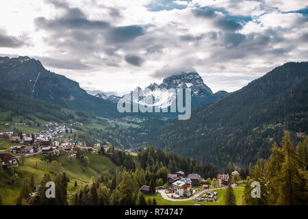 Paisaje con pueblos del valle y de las montañas cubiertas de nieve, Dolomitas, Italia Imagen De Stock