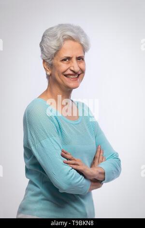 Retrato de mujer mayor confianza de pie con los brazos cruzados. Imagen De Stock