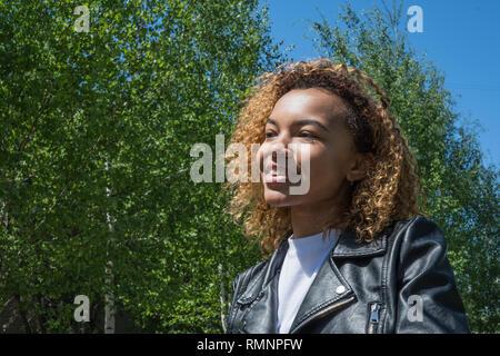 Hermosa muchacha africana modelo posando en la primavera de perfil en la calle Imagen De Stock