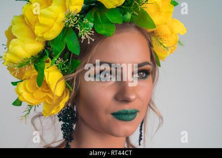 Cara cerca de una hermosa niña con maquillaje brillante y grandes flores amarillas en la cabeza Imagen De Stock