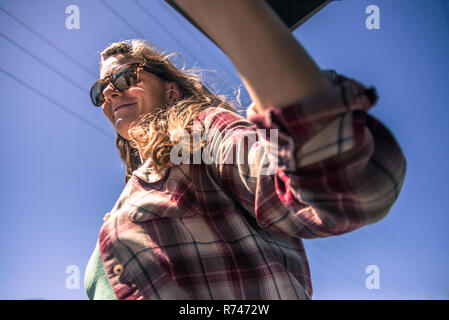 Mujer joven en anteojos oscuros contra el cielo azul, vista de ángulo bajo Imagen De Stock