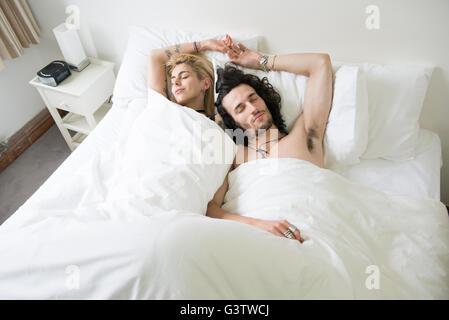 Un fresco joven pareja relajante en la cama con los ojos cerrados. Imagen De Stock