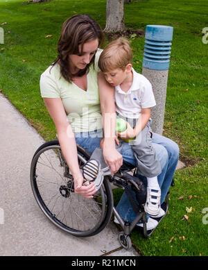 Mamá discapacitados en silla de ruedas ayudando pequeño muchacho puso en la zapata. © Myrleen Pearson ......Ferguson Cate Imagen De Stock