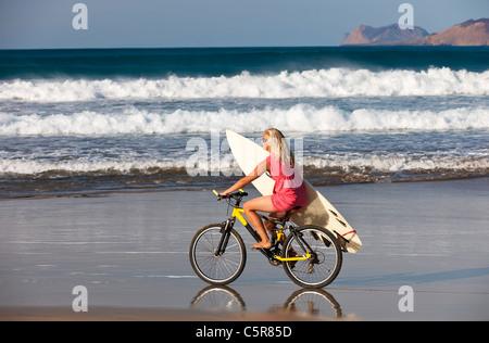 Surfer girl cabalga las olas del mar en bicicleta de montaña. Imagen De Stock
