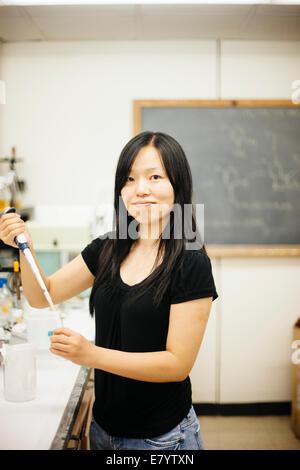 Mujer en el laboratorio usando una pipeta y tubo de vidrio de llenado Imagen De Stock