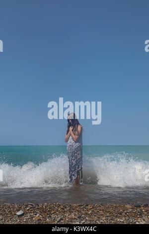 Una niña de pie en un lago en las ondas Imagen De Stock