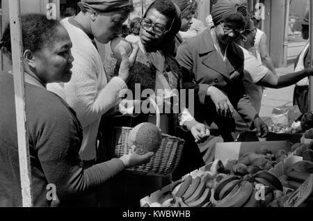Londres Multicultural 1970 Reino Unido, las mujeres comprando frutas de un puesto en el mercado de Londres, Inglaterra Imagen De Stock