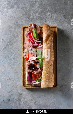 Baguette de carne con tomate, albahaca, cebolla roja madera sirve en servir a bordo de textura gris de fondo. Espacio laical, plana Imagen De Stock