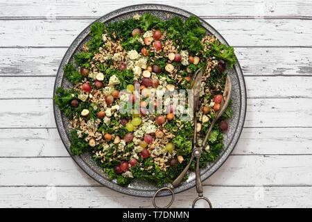 Ensalada de col rizada con mezcla de cereales, frutos secos y uvas. Imagen De Stock