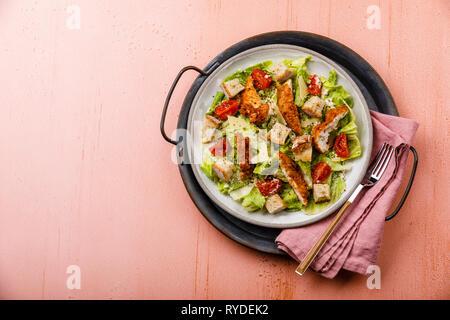 Ensalada César con pollo en bandeja de metal sobre fondo de color rosa espacio de copia Imagen De Stock