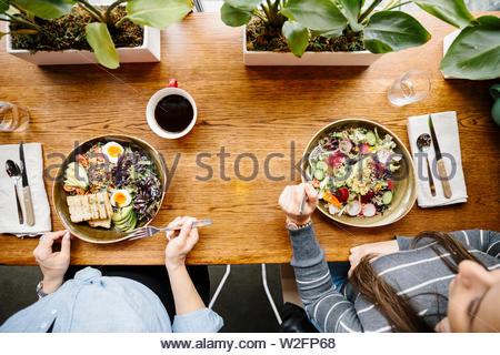 Vista desde arriba de la mujer comiendo ensaladas en la mesa de restaurante Imagen De Stock