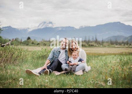 Retrato sonriente padres e hijo sentado en el ámbito rural con montañas en segundo plano. Imagen De Stock