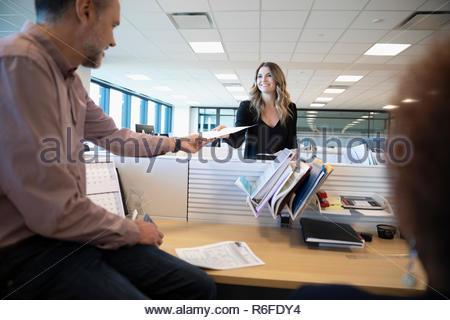 Gente de negocios pasando el papeleo sobre el armario de oficina Imagen De Stock