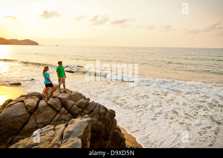 Pareja con perro senderismo en las rocas de la playa Imagen De Stock