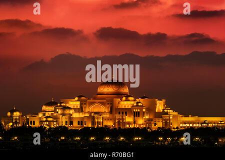 Hermoso atardecer en el palacio presidencial de Emiratos Árabes Unidos en Abu Dhabi. Las nubes parecen montañas en el fondo. Imagen De Stock