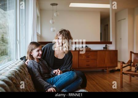 Madre e hija pegado en el sofá de la sala Imagen De Stock
