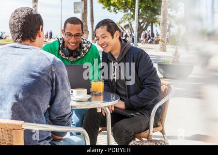 Amigos varones con portátil en la acera soleada cafetería Imagen De Stock