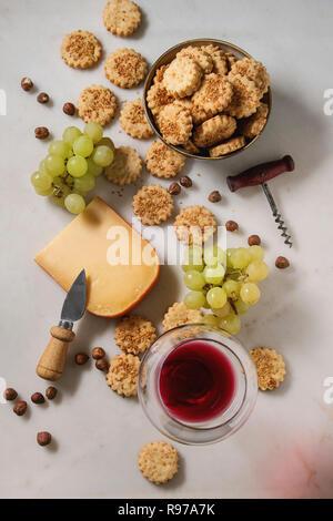 Aperitivo de vino. Queso, uvas, nueces, galletas de queso galletas con un vaso de vino tinto y la cuchilla sobre fondo de mármol blanco. Espacio laical, plana Imagen De Stock