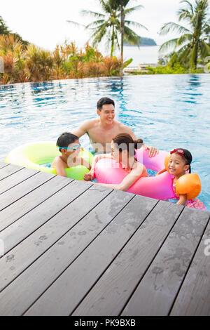 Feliz joven familia divirtiéndose en la piscina Imagen De Stock