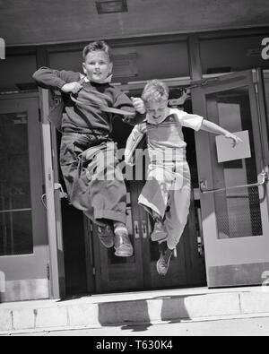 1950 dos chicos ejecutando saltando fuera de las puertas de la escuela primaria - S617 HAR001 HARS SALUBRIDAD COPIA DE LONGITUD COMPLETA AMISTAD ESPACIO inspiración liberar machos Hermanos confianza B&W LIBERTAD ESCUELAS GRADO felicidad alegre aventura SALTO DE EMOCIÓN AL HERMANO PRIMARIA GRATUITA escapar sonrisas alegres AMABLE K-12 panorámica liberada la escuela primaria El crecimiento menores compañeros COMPAÑERISMO EN BLANCO Y NEGRO la etnia CAUCÁSICA COMPAÑEROS HAR001 ANTICUADO Imagen De Stock
