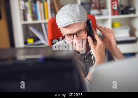 Mitad hombre adulto sonriente mientras utilizando el teléfono Imagen De Stock
