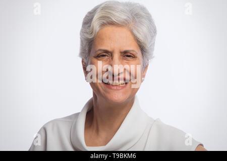 Retrato de mujer de pie senior contra el fondo blanco. Imagen De Stock