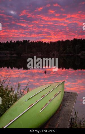 Canoa y hermoso atardecer por el lago Vansjø, Østfold, Noruega. Imagen De Stock