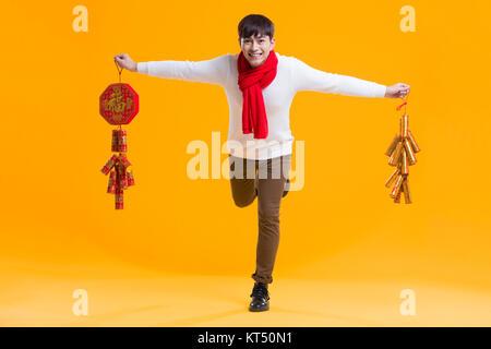Joven alegre celebrando el Año nuevo chino con petardos Imagen De Stock