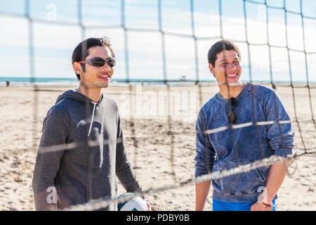 Los hombres sonrientes jugando voleibol de playa en sunny beach Imagen De Stock