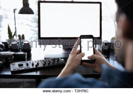 Fotógrafo macho usando smart phone en el escritorio Imagen De Stock