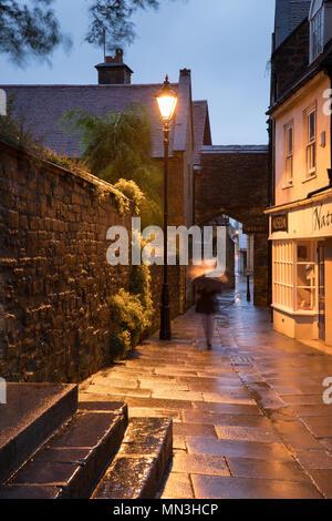 Mujer en la lluvia en una tarde de verano, Sherborne, Dorset, Inglaterra, Reino Unido. Imagen De Stock