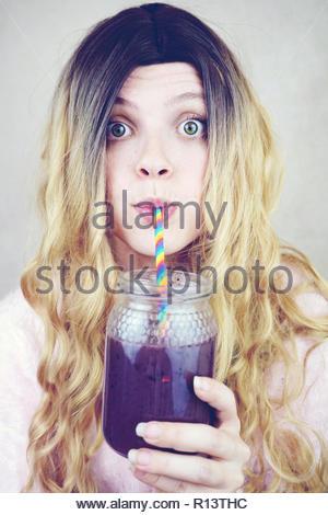Retrato de una joven y bella mujer bebiendo de un tarro de vidrio Imagen De Stock