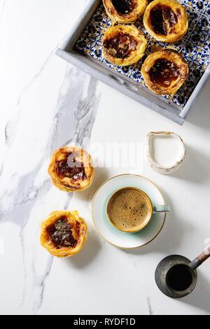 Tarta de huevo tradicional portuguesa Pasteis postre Pastel de nata en azulejo clásico bandeja con una taza de café negro y la jarra de leche en mármol blanco backgro Imagen De Stock