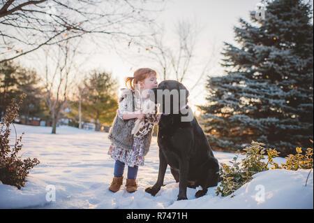Hembra con pelo rojo niño jugando en la nieve con perros, Keene, Ontario, Canadá Imagen De Stock