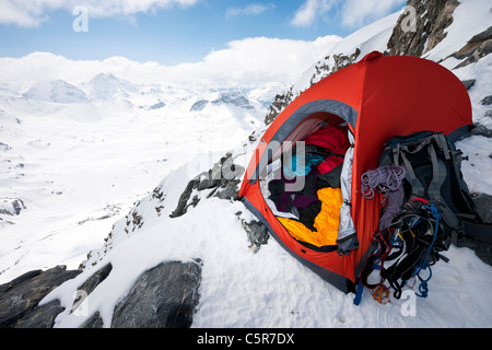 Los montañeros una carpa en el borde de una alta montaña alpina. Imagen De Stock